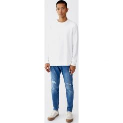 Średnioniebieskie jeansy carrot fit. Niebieskie jeansy męskie relaxed fit Pull&Bear. Za 139,00 zł.