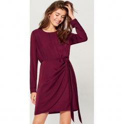 Satynowa sukienka z wiązaniem - Różowy. Czerwone sukienki z falbanami marki Mohito, z satyny. W wyprzedaży za 79,99 zł.