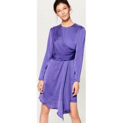 Kopertowa sukienka z satynowym połyskiem - Fioletowy. Fioletowe sukienki z falbanami marki Mohito, z satyny, z kopertowym dekoltem, kopertowe. W wyprzedaży za 99,99 zł.