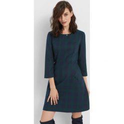 Trapezowa sukienka w kratę. Zielone sukienki hiszpanki Orsay, na lato, z poliesteru, z dekoltem na plecach, trapezowe. Za 139,99 zł.
