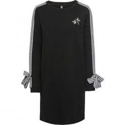 Sukienka dresowa z kokardkami i aplikacją bonprix czarny. Czarne sukienki dresowe marki bonprix, w kolorowe wzory. Za 109,99 zł.