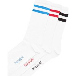 Długie skarpetki z kolorowymi paskami. Białe skarpetki męskie Pull&Bear, w kolorowe wzory. Za 39,90 zł.