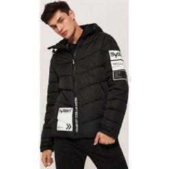 Pikowana kurtka z nadrukami - Czarny. Czarne kurtki męskie pikowane marki KIPSTA, z poliesteru, do piłki nożnej. Za 229,99 zł.