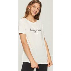 T-shirt z napisem - Kremowy. Białe t-shirty damskie marki Sinsay, l, z napisami. W wyprzedaży za 14,99 zł.