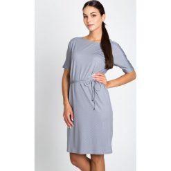 Szara wiązana sukienka w mikrowzór QUIOSQUE. Szare sukienki dzianinowe marki QUIOSQUE, na co dzień, w geometryczne wzory, z krótkim rękawem, mini, proste. W wyprzedaży za 79,99 zł.