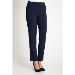 Granatowe eleganckie spodnie z kieszeniami na biodrach QUIOSQUE. Brązowe rurki damskie marki QUIOSQUE, z bawełny, z standardowym stanem, midi, dopasowane. W wyprzedaży za 159,99 zł.
