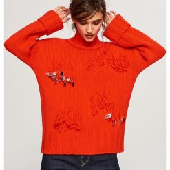 Sweter z frędzlami i cekinami - Pomarańczo. Czerwone swetry klasyczne damskie marki Lemoniade, na lato, ze splotem, z asymetrycznym kołnierzem. Za 159,99 zł.