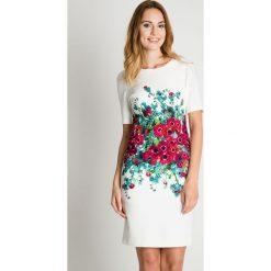 Klasyczna biała sukienka z kwiatową aplikacją BIALCON. Białe sukienki BIALCON, na co dzień, z aplikacjami, klasyczne, z kopertowym dekoltem, kopertowe. Za 335,00 zł.