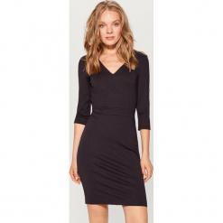 Dopasowana sukienka z dekoltem w szpic - Czarny. Czarne sukienki z falbanami marki Mohito, l, dopasowane. Za 119,99 zł.
