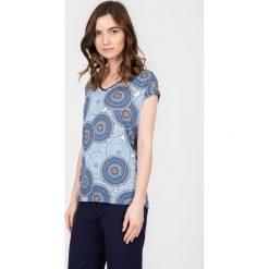 Niebieska bluzka z orientalnym wzorem QUIOSQUE. Niebieskie bluzki z odkrytymi ramionami QUIOSQUE, z nadrukiem, z dekoltem w serek, z krótkim rękawem. W wyprzedaży za 39,99 zł.