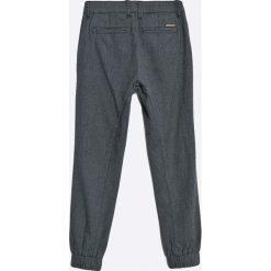 Guess Jeans - Spodnie dziecięce 118-175 cm. Szare jeansy męskie z dziurami marki Guess Jeans, z aplikacjami, z bawełny. W wyprzedaży za 149,90 zł.