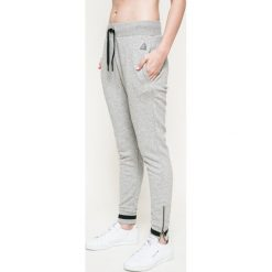 Reebok - Spodnie. Szare spodnie sportowe damskie marki Reebok, l, z dzianiny, z okrągłym kołnierzem. W wyprzedaży za 169,90 zł.