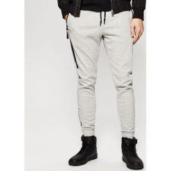 Spodnie dresowe męskie: Dresowe joggery z taśmami - Szary