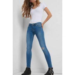 Jeansy skinny z przetarciem. Niebieskie jeansy damskie skinny marki Orsay, z bawełny. W wyprzedaży za 60,00 zł.