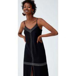 Sukienka z kontrastowymi szwami. Czarne sukienki z falbanami Pull&Bear, z kontrastowym kołnierzykiem. Za 62,90 zł.