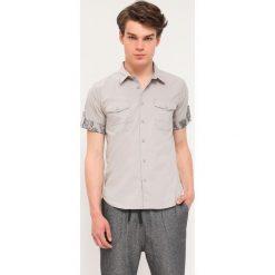 KOSZULA KRÓTKI RĘKAW MĘSKA. Brązowe koszule męskie marki QUECHUA, m, z elastanu, z krótkim rękawem. Za 29,99 zł.