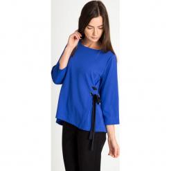Kobaltowa bluzka z bocznym wiązaniem QUIOSQUE. Niebieskie bluzki ażurowe QUIOSQUE, ze skóry ekologicznej, klasyczne, z kopertowym dekoltem, z krótkim rękawem. W wyprzedaży za 69,99 zł.