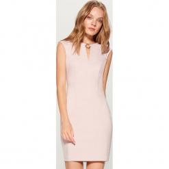 Sukienka z ozdobną klamrą - Różowy. Różowe sukienki z falbanami marki numoco, l, z dekoltem w łódkę, oversize. Za 159,99 zł.