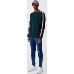 Ciemnoniebieskie jeansy rurki. Szare jeansy męskie Pull&Bear. Za 139,00 zł.