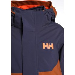 Helly Hansen UNIVERS  Kurtka snowboardowa cinnamon. Brązowe kurtki chłopięce sportowe marki Reserved, l, z kapturem. W wyprzedaży za 468,30 zł.
