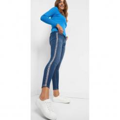 Jeansy z ozdobnymi lampasami. Niebieskie jeansy damskie skinny Orsay. Za 99,99 zł.
