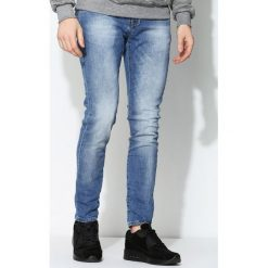Niebieskie Jeansy Decline. Czarne jeansy męskie z dziurami marki Born2be, l, z aplikacjami, z dresówki. Za 64,99 zł.