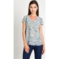 Zwiewna miętowa bluzka w geometryczny wzór QUIOSQUE. Zielone bluzki damskie marki QUIOSQUE, w geometryczne wzory, z dekoltem w serek, z krótkim rękawem. W wyprzedaży za 59,99 zł.