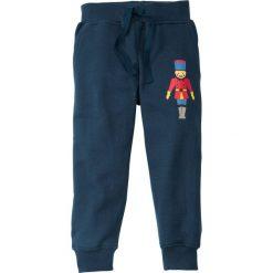 Bożonarodzeniowe spodnie dresowe bonprix ciemnoniebieski z nadrukiem. Niebieskie spodnie chłopięce marki bonprix, z nadrukiem, z dresówki. Za 24,99 zł.