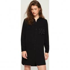 Koszulowa sukienka z aplikacją - Czarny. Czarne sukienki z falbanami marki Mohito, m, z kontrastowym kołnierzykiem. Za 79,99 zł.
