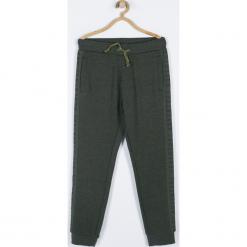 Spodnie. Brązowe chinosy chłopięce TRAVELLER, z nadrukiem, z bawełny. Za 79,90 zł.