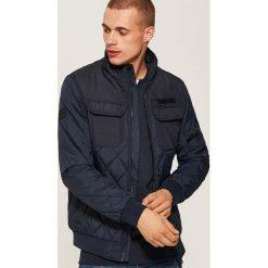 Pikowana kurtka - Granatowy. Czarne kurtki męskie pikowane marki KIPSTA, z poliesteru, do piłki nożnej. Za 149,99 zł.