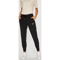 Nike Sportswear - Spodnie. Różowe spodnie sportowe damskie marki Nike Sportswear, l, z nylonu, z okrągłym kołnierzem. Za 259,90 zł.