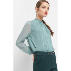 Bluzka ze stójką. Zielone bluzki asymetryczne Orsay, z dzianiny, eleganckie, z falbankami. W wyprzedaży za 60,00 zł.