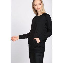 Czarna Bluza Demonic. Czarne bluzy sportowe damskie marki DOMYOS, z elastanu. Za 49,99 zł.