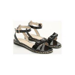 Czarne Sandały Puddle. Czarne sandały damskie marki Born2be, z lakierowanej skóry, na płaskiej podeszwie. Za 39,99 zł.
