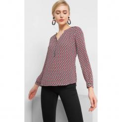 Bluzka z geometrycznym wzorem. Czerwone bluzki asymetryczne Orsay, w geometryczne wzory, z elastanu, dekolt w kształcie v. Za 69,99 zł.