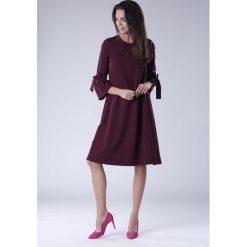 Bordowa Trapezowa Sukienka Wizytowa z Efektownym Rękawem. Czerwone sukienki koktajlowe marki Molly.pl, do pracy, l, z kokardą, oversize. W wyprzedaży za 138,48 zł.
