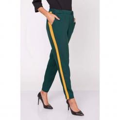 Spodnie w kolorze ciemnozielonym. Zielone spodnie z wysokim stanem marki Moda w jesiennych kolorach, w paski. W wyprzedaży za 89,95 zł.