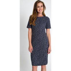 Szara klasyczna sukienka z czarnym wzorem QUIOSQUE. Czarne sukienki balowe QUIOSQUE, z dzianiny, z klasycznym kołnierzykiem, z długim rękawem, midi, dopasowane. W wyprzedaży za 139,99 zł.