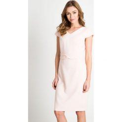 Jasnoróżowa sukienka z kokardą QUIOSQUE. Białe sukienki balowe marki QUIOSQUE, na spotkanie biznesowe, na lato, w paski, z satyny, z kopertowym dekoltem, kopertowe. W wyprzedaży za 99,99 zł.