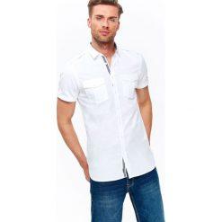 KOSZULA MĘSKA GŁADKA Z KONTRASTOWYMI WSTAWKAMI O DOPASOWANYM KROJU. Brązowe koszule męskie marki QUECHUA, m, z elastanu, z krótkim rękawem. Za 34,99 zł.
