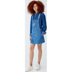 Jeansowa sukienka ogrodniczka z niewykończonym dołem. Niebieskie sukienki z falbanami Pull&Bear, z jeansu. Za 89,90 zł.