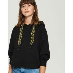 Bluza z nadrukiem Batman - Czarny. Fioletowe bluzy z nadrukiem damskie marki Reserved, l, z kapturem. Za 69,99 zł.
