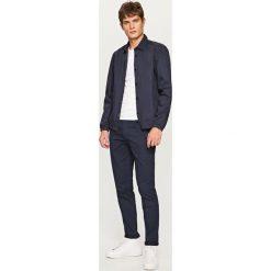 Spodnie slim fit - Granatowy. Niebieskie spodnie chłopięce marki Reserved. W wyprzedaży za 99,99 zł.