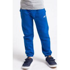 Spodnie dresowe dla małych chłopców JSPMD101 - niebieski. Niebieskie spodnie chłopięce marki 4F JUNIOR, na lato, z bawełny. Za 29,99 zł.