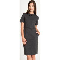 Czarna elegancka sukienka z kołnierzykiem QUIOSQUE. Czarne sukienki mini marki QUIOSQUE, do pracy, z dzianiny, biznesowe, z dekoltem na plecach, z krótkim rękawem, dopasowane. W wyprzedaży za 59,99 zł.