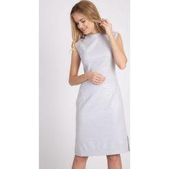 Błyszcząca szara sukienka z rozporkiem QUIOSQUE. Szare sukienki balowe marki QUIOSQUE, s, w geometryczne wzory, z dzianiny, z kopertowym dekoltem, bez rękawów, kopertowe. W wyprzedaży za 79,99 zł.