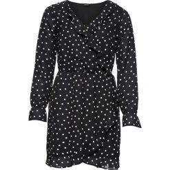 Sukienka z efektem założenia kopertowego  z falbanami bonprix czarny w białe kropki. Czarne sukienki na komunię marki bonprix, w kropki, z kopertowym dekoltem, kopertowe. Za 89,99 zł.