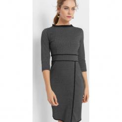 Dopasowana sukienka żakardowa. Czarne sukienki asymetryczne marki Orsay, w geometryczne wzory, z dzianiny, z asymetrycznym kołnierzem. Za 119,99 zł.
