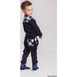 Granatowe spodnie dresowe krata. Szare chinosy chłopięce Pakamera, z bawełny. Za 60,00 zł.
